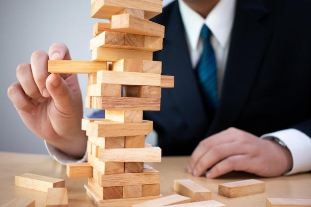 ビジネス旅行者は、木製ブロックギャンブルの塔でビジネス、ビジネス、およびプロジェクトエンジニアのリスク管理を計画および戦略しています。