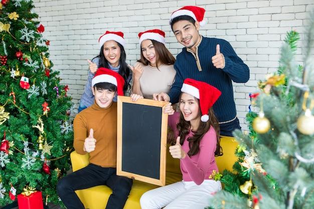 アジアの友人のグループは、クリスマスのお祝いで空白の看板を保持し、自宅で幸せな新年を楽しみました。