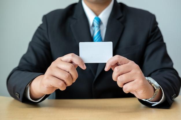 Деловые люди носят костюмы, сидя за партами и показывая белую карточку