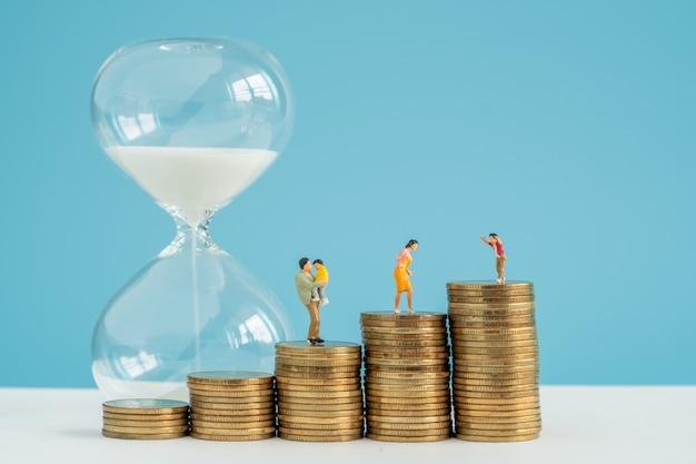 Песочные часы и стек монеты со значительными сбережениями внутри семьи