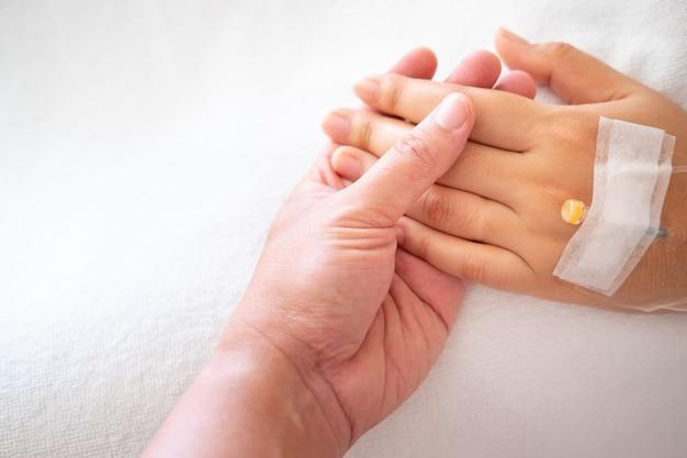 病院で女性の手を握って男。病院で病気の女性。医療コンセプトを持つ人々。