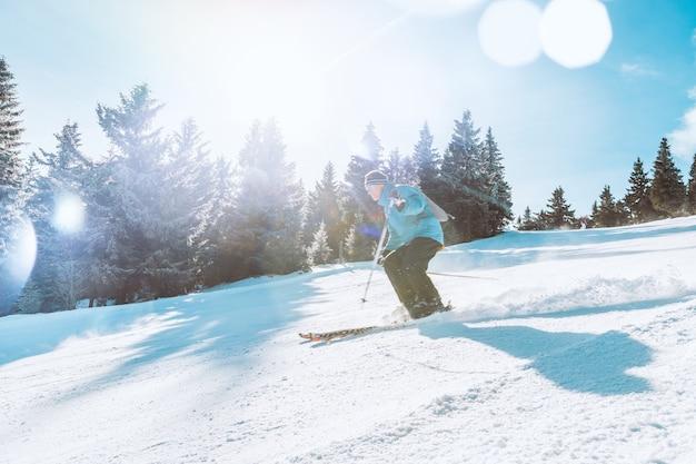 高山で晴れた日の下り坂をスキーヤーでスキー