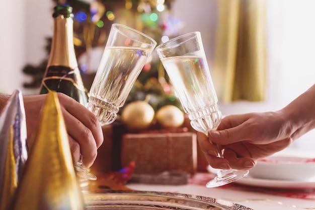 女性と男性の手はシャンパンの眼鏡でトースト