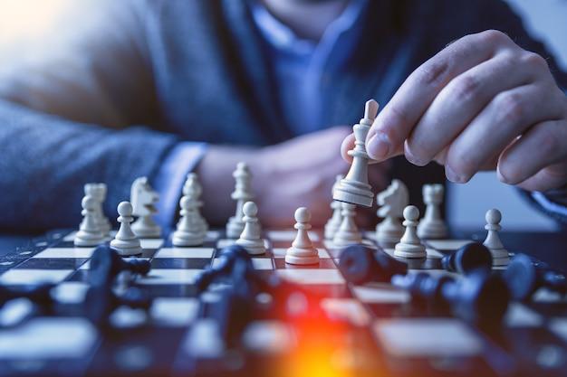 チェス金融ビジネス戦略の概念。チェスの部分を保持するチームリーダー。