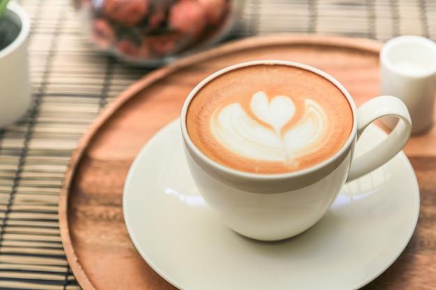 Горячий кофе латте на деревянном подносе с теплым светом