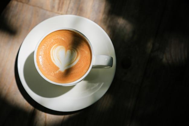 ローライトの木の床にラテコーヒー