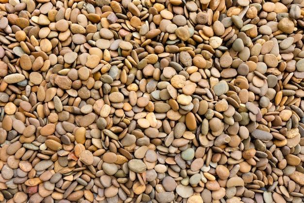 小石の石または玉石の石の自然な茶色の織り目加工の背景