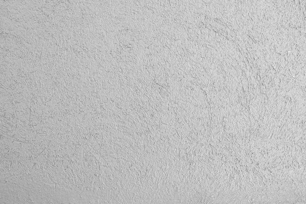 Серая штукатурка цемента стены фоновой текстуры пустой.