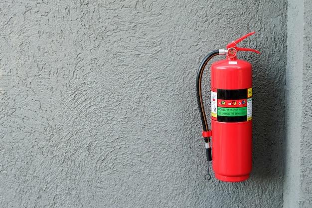 灰色のセメント壁の消火器。