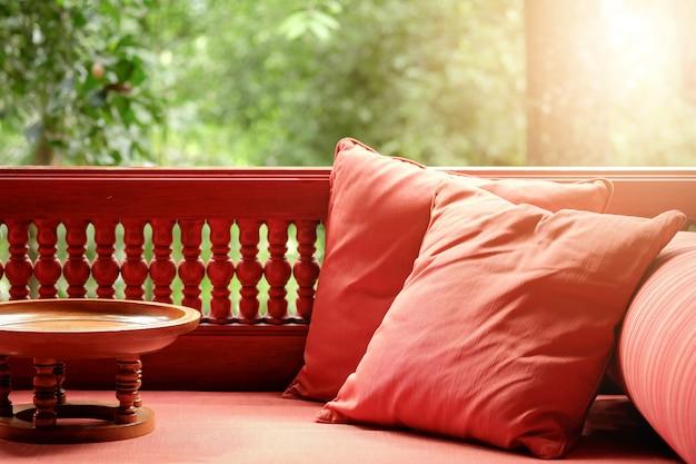 枕と小さな木製テーブルのあるテラス席。ナチュラルフレッシュグリーン
