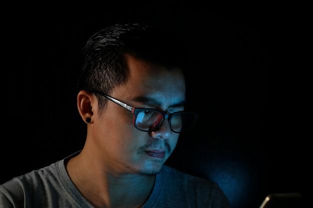アジアの男性は、暗闇の中で青い光、技術の概念効果で携帯電話またはタブレットを使用しています。
