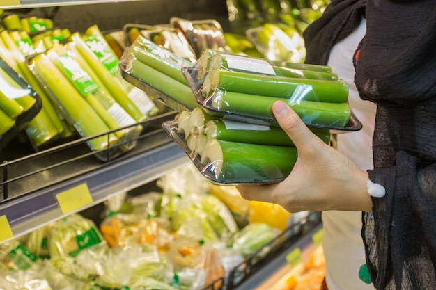女性が市場で野菜を選ぶ