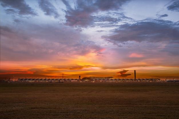 タイの空港バンコクで金の芝生の上の光に沈む夕日。
