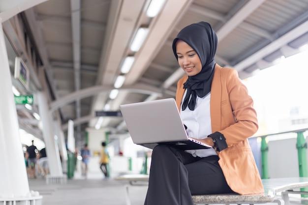 ノートパソコンでスカイトレインで働く美しい若いアジアの女の子。イスラム教徒の女性