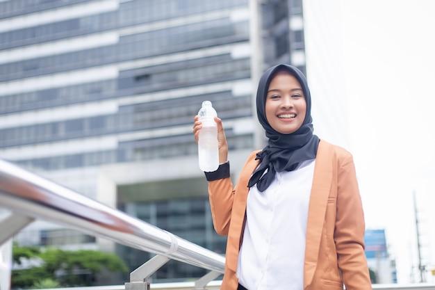 美しい若いアジアのイスラム教徒の飲料水。