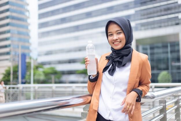 ボトル入りの水と美しい若いアジアのイスラム教徒。