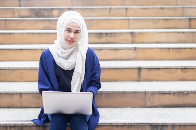 Красивые мусульманские деловые женщины в хиджабе с ноутбуком, работающим на открытом воздухе.