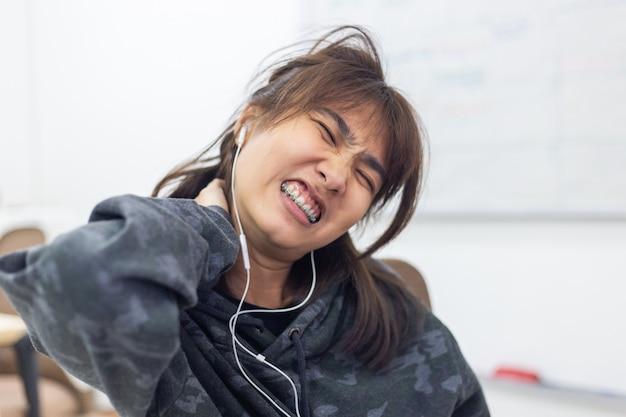 アジアの女性の首の痛みとヘッドフォン。