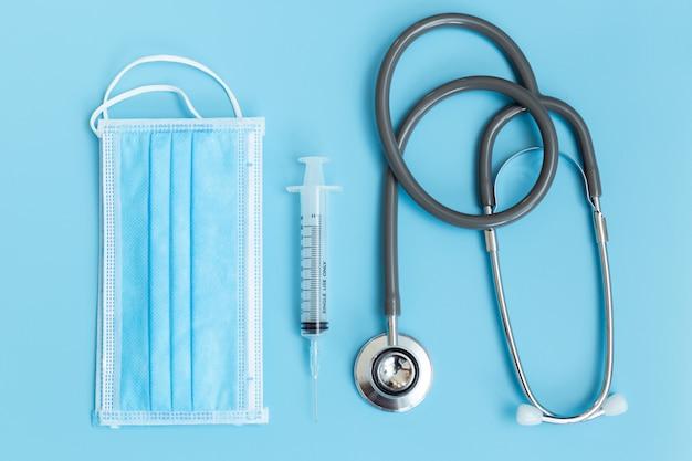 医療用聴診器シリンジと青いテーブルの衛生マスク保護ウイルス。