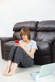 在宅勤務の携帯電話を使用してアジアの女性。