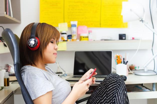 自宅で携帯電話の仕事を使用してヘッドフォンを身に着けているアジアの女性。