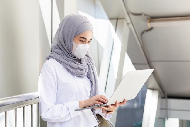 Азиатская мусульманская коммерсантка нося медицинскую маску для предотвращает вирус пыли и инфекции работая с компьтер-книжкой на пути идет к офису.