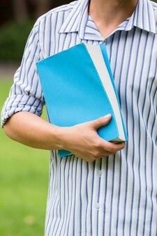 Человек, держащий синий учебник