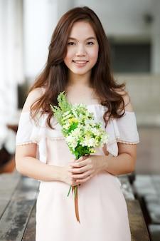 彼女の手に花を抱く若いアジア人女性