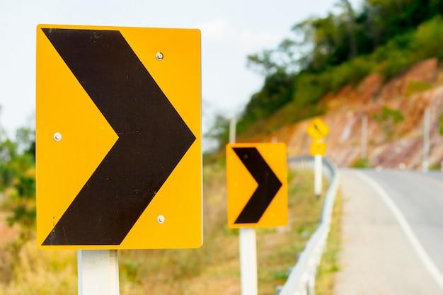 湾曲した道路から黄色い警告危険サイン