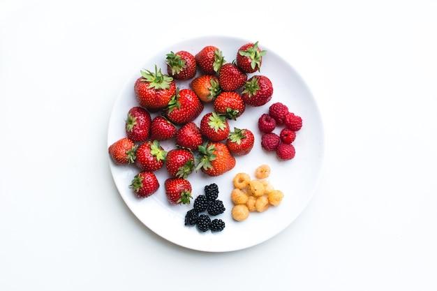 Воздушный выстрел из красочных здоровых свежих ягод на тарелке на белом фоне