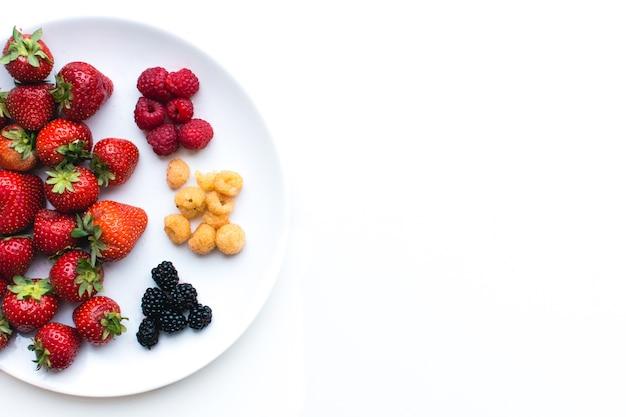 白い背景にプレートにカラフルな健康的な新鮮な果実の空撮