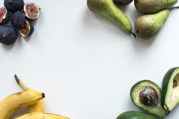 白い背景に新鮮なイチジク、バナナ、梨、アボカドの航空ショット