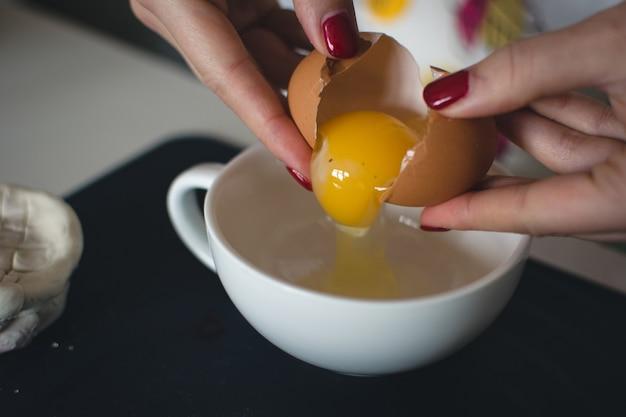 ベーキングのために卵を割る