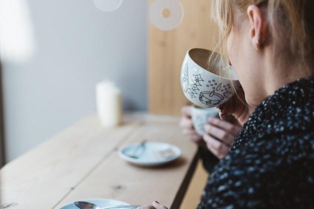 Девушка потягивая кофе