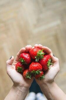 彼女の手に新鮮な熟したイチゴを持っている女性