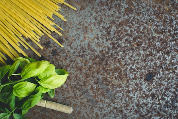 錆びた金属の背景にバジルと木製スプーンのパスタスパゲッティ
