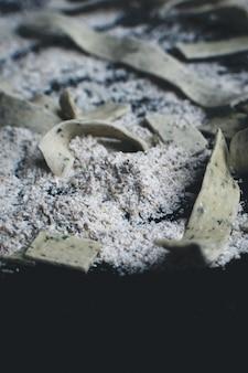 黒の背景に小麦粉で覆われたパスタタリアテッレ