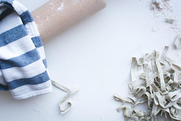 白い背景に木製のローラーで小麦粉で覆われたパスタ・タリアテッレ