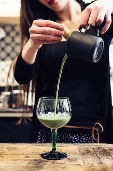 ガラスに緑茶抹茶カクテルを注ぐ