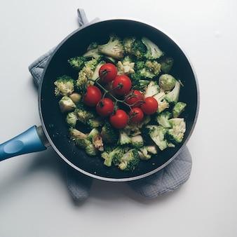Перемешать жареную брокколи, брюссельскую капусту и помидоры черри
