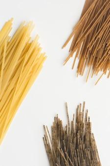Цельнозерновые макароны спагетти триколора на белом фоне