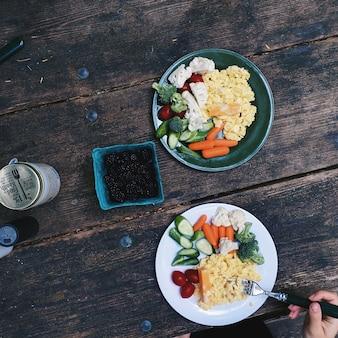 キャンプ中に朝食のための野菜とスクランブルエッグ
