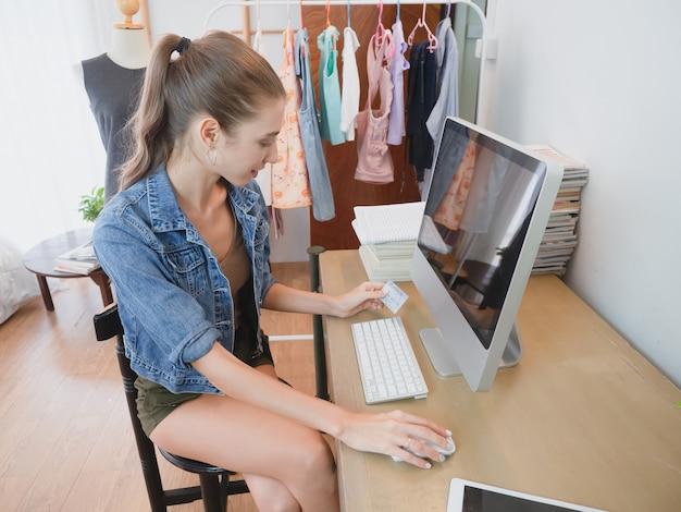 女性はコンピューターを介して顧客の質問に答えています