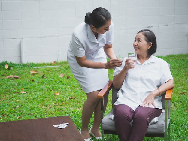 看護師は幸せな高齢者の世話をしており、年配の女性は水で薬を食べる