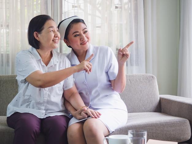 看護師は幸せで高齢者の世話をしており、介護者は年配の女性の手に手を置いた