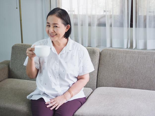 高齢者はコーヒーを飲んで幸せに座る