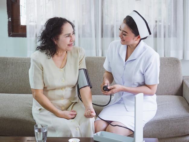看護師は幸せな高齢者の世話をしており、女性は高齢者の圧力を測定しています