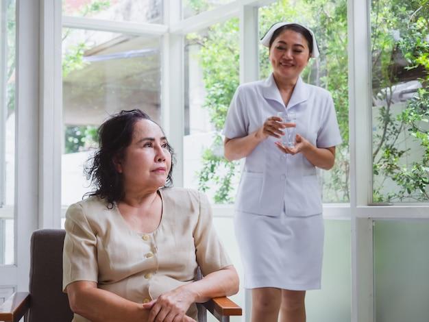 看護師は幸せな高齢者の世話をしています。老婦人は何かを考えています