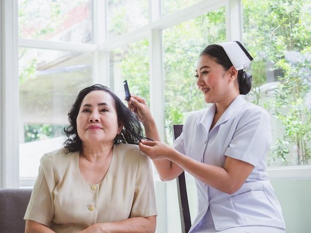 看護師は幸せな高齢者の髪をとかす