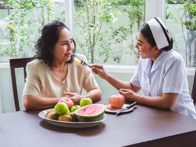 看護師はリンゴを高齢者に与えています